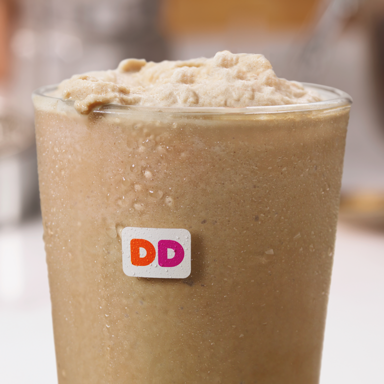 Dunkin' Donuts Frozen Iced Coffee with whipped cream on a table.